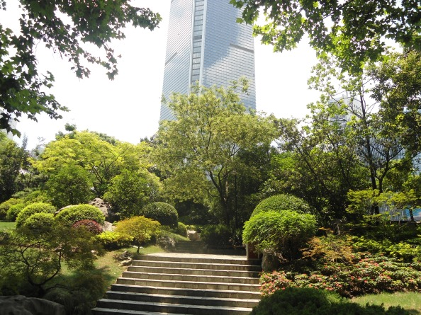 A skyscraper looking over a garden in Shanghai, China